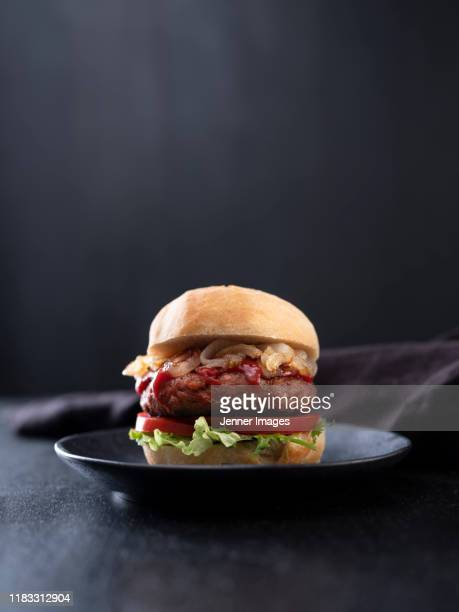 vegan burger on black plate. - burger stock pictures, royalty-free photos & images