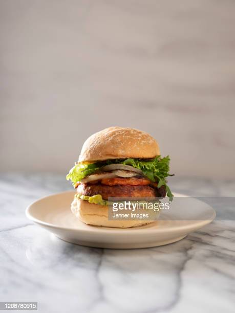 vegan burger sitting on a marble bench. - veggie burgers stock pictures, royalty-free photos & images