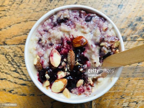 vegan coconut 5-grain porridge pot with compote and almonds - sergio amiti stock pictures, royalty-free photos & images