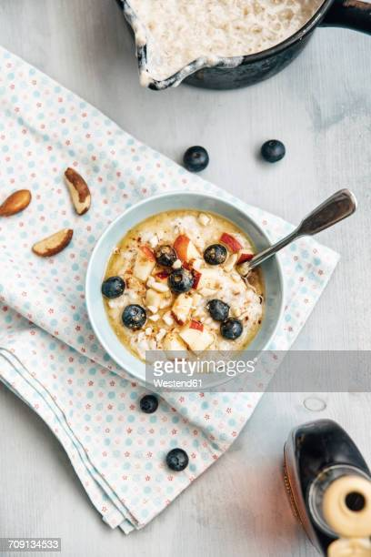 Vegan coconut milk porridge with blueberries, apple, brazil nuts and cinnamon