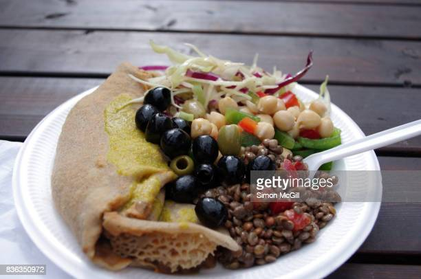 Vegan Ethiopian street food including injera, a sourdough flatbread filled with 3 sauces, and assorted salads, on a polystyrene plate on a wooden outdoor table at the Truman Brewery Building, Brick Lane, East London, England