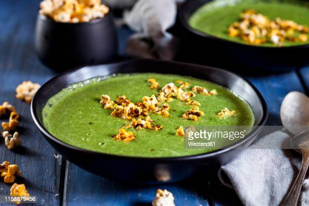 vegan green vegetable soup with spinach, leek and peas, chili popcorn - soup bowl stock pictures, royalty-free photos & images