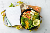 Vegan healthy balanced diet Vegetarian buddha bowl with blank notebook and measuring tape. hickpeas, broccoli, pepper, tomato, spinach, arugula and avocado in plate on white background. Top view