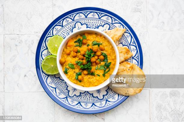 vegan lentil curry with red lentils, sweet potatoes, spinach, roasted turmeric, chickpeas, with lime juice and coriander and naan bread - spinach stock pictures, royalty-free photos & images