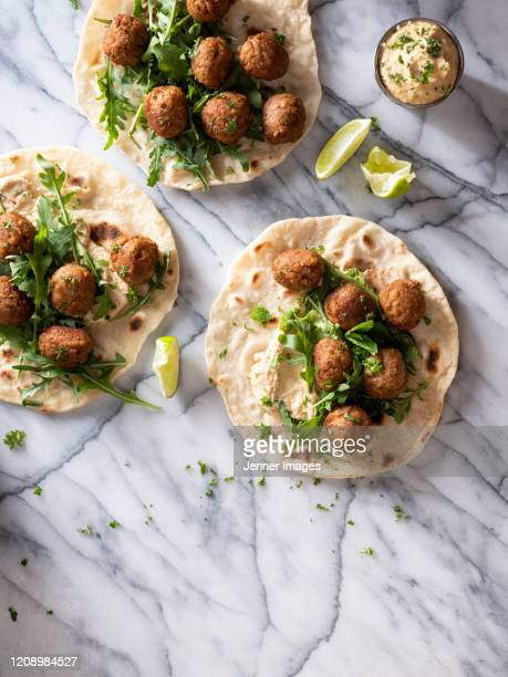 vegan meatballs on flatbreads with hummus dip and rocket leaves. - vegetarianism stock pictures, royalty-free photos & images