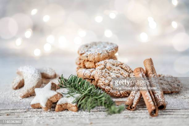 vegan oatmeal cookies with powdered sugar, cinnamon sticks and cinnamon stars on a wooden table at christmas. - tina terras michael walter stock-fotos und bilder