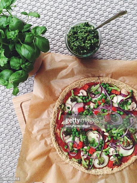 Vegan pizza with a chickpea crust, vegetables and pesto