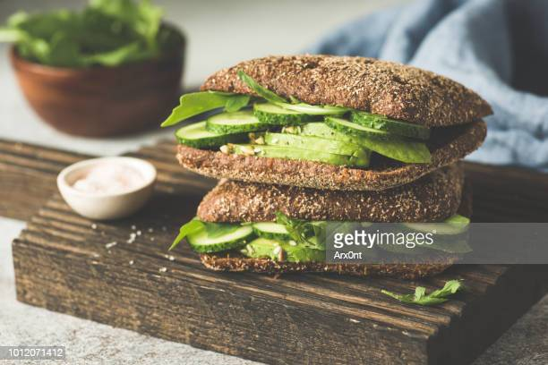 vegan rye sandwich with avocado and cucumber - sandwich stock pictures, royalty-free photos & images