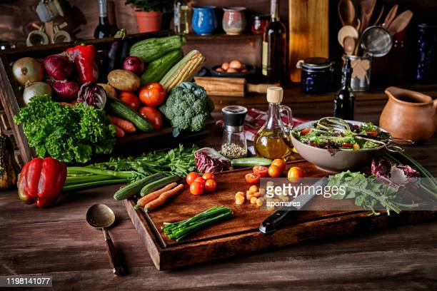 vegan salad making in rustic kitchen with assorted organic vegetables. natural lighting - salad bowl stock pictures, royalty-free photos & images