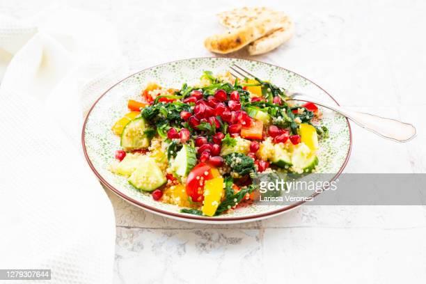 vegan salad with quinoa and pomegranate seeds - larissa veronesi stock-fotos und bilder