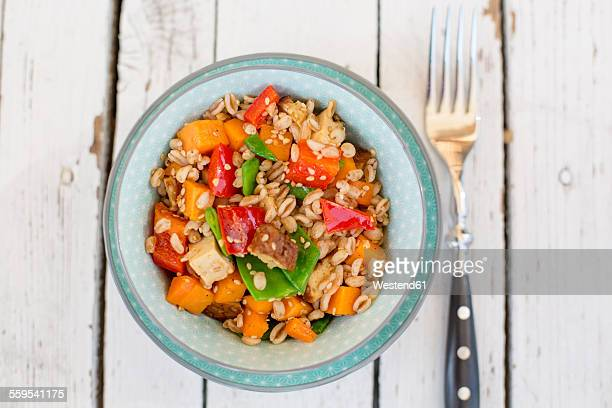 Vegan salad with spelt wheat, sesame, tofu, red bell pepper, snow peas and carrots
