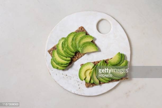 Vegan sandwiches with sliced avocado on rye bread served on ceramic board over white marble background Flat lay space