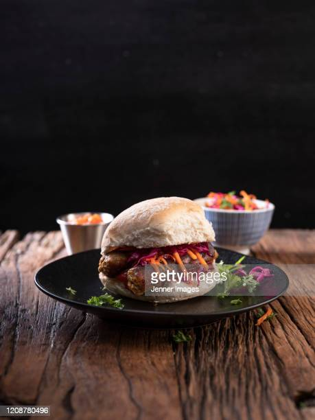 vegan sausages in a bread bun with coleslaw and salsa. - plate stock pictures, royalty-free photos & images