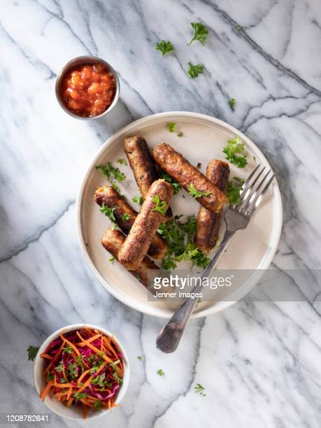 vegan sausages on a white plate with coleslaw and salsa. - sausage stock pictures, royalty-free photos & images