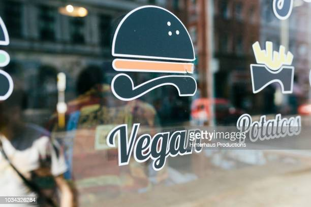 vegan sign on restaurant window - vegana fotografías e imágenes de stock