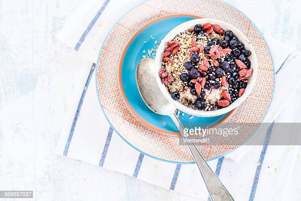 Vegan superfood breakfast with porridge, almond milk, blueberries, roasted quinoa, and goji berries