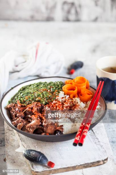 Vegan teriyaki bowl with pulled teriyaki beef made from jackfruit, spinach, rice and carrots