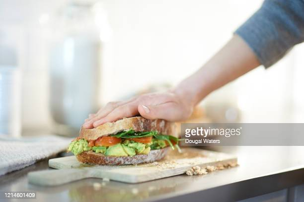 vegan wholemeal bread sandwich with smashed avocado, spinach and tomato filling. - sandwich stock pictures, royalty-free photos & images