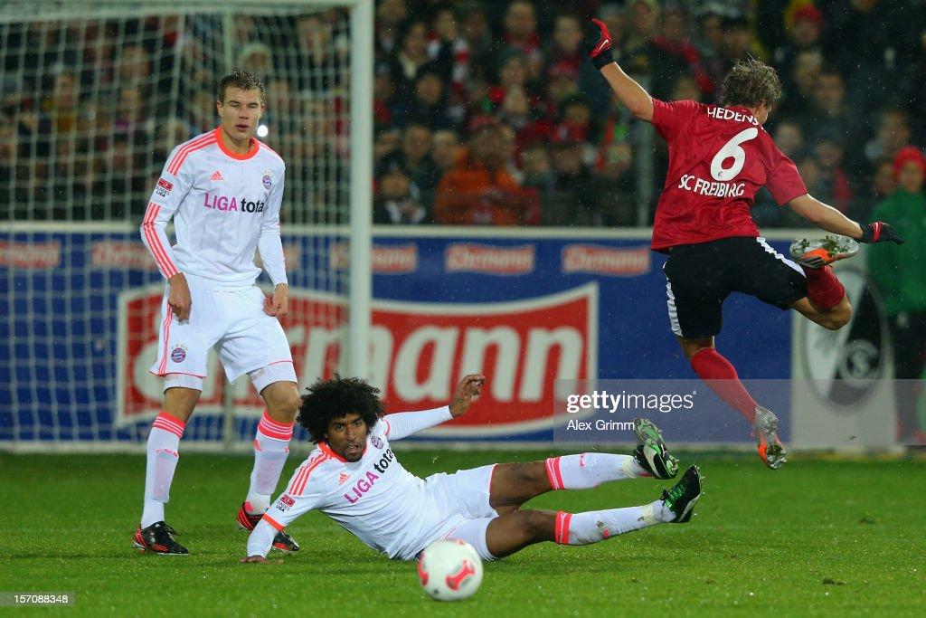 Vegar Hedenstad of Freiburg is challenged by Dante of Muenchen during the Bundesliga match between SC Freiburg and FC Bayern Muenchen at MAGE SOLAR Stadium on November 28, 2012 in Freiburg im Breisgau, Germany.