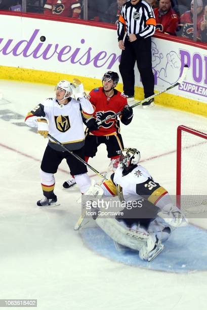 Vegas Golden Knights Defenceman Nick Holden attempts to bat the puck out of the air while Calgary Flames Left Wing Johnny Gaudreau and Vegas Golden...