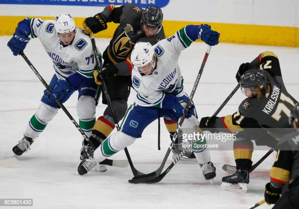 Vegas Golden Knights defenseman Brayden McNabb and center William Karlsson battle Vancouver Canucks right wing Brock Boeser for control of the puck...