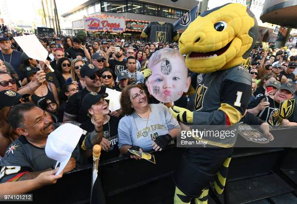 Vegas Golden Knights fan Miguel Sierra of Nevada watches as the Vegas Golden Knights mascot Chance the Golden Gila Monster signs his Halloween baby...