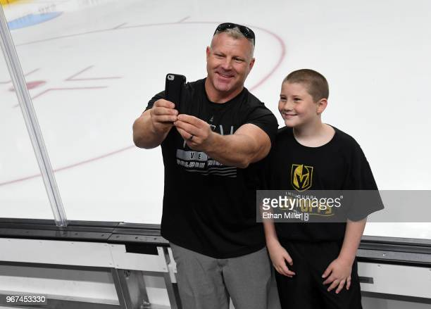 Vegas Golden Knights fans Darrell Garvin and his son Gage Garvin both of Nevada pose for selfies next to the boards during a Golden Knights road game...