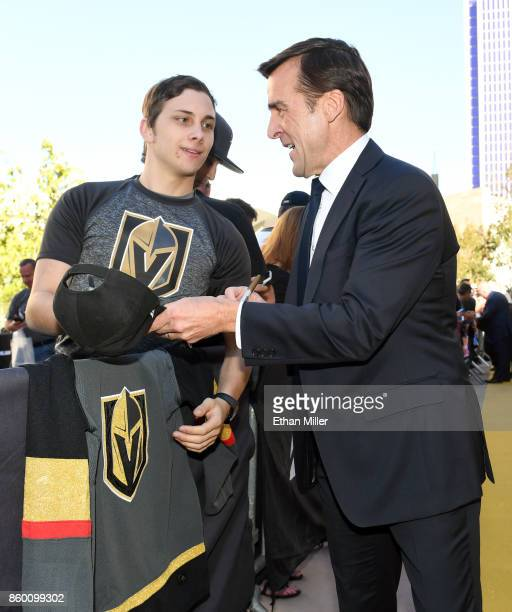 Vegas Golden Knights general manager George McPhee signs autographs for fans as he arrives at the team's inaugural regularseason home opener against...