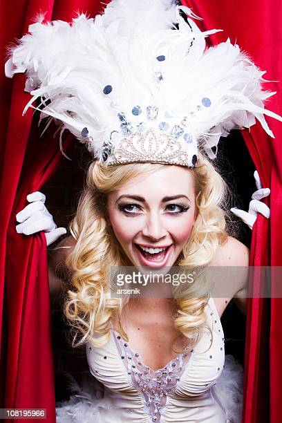 Vegas Showgirl in Costume Peeking Through Red Curtains