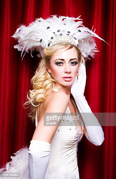 Vegas Showgirl in Costume Standing Against Red Curtains