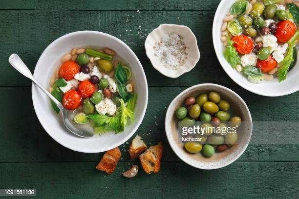 vegetable broth with spinach, herb, cannellini beans and greek olives - kalamata olive stock photos and pictures