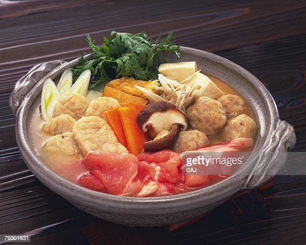 Vegetable, fried fish balls and pork in pot, high angle view