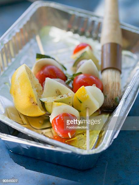 Vegetable kebabs in aluminium dish with oil and brush