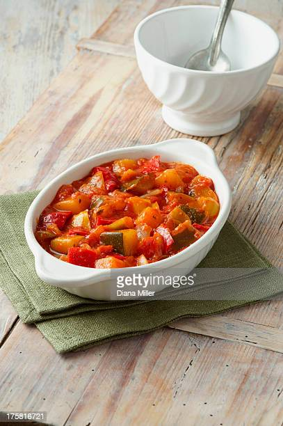 Vegetable ratatouille. Courgettes, tomatoes and red and yellow peppers in white dish on a green cloth
