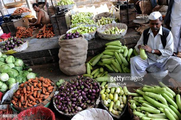Vegetable seller works at a market in Mumbai on March 26, 2009. Inflation in India edged closer to zero, official data showed, raising fears of...
