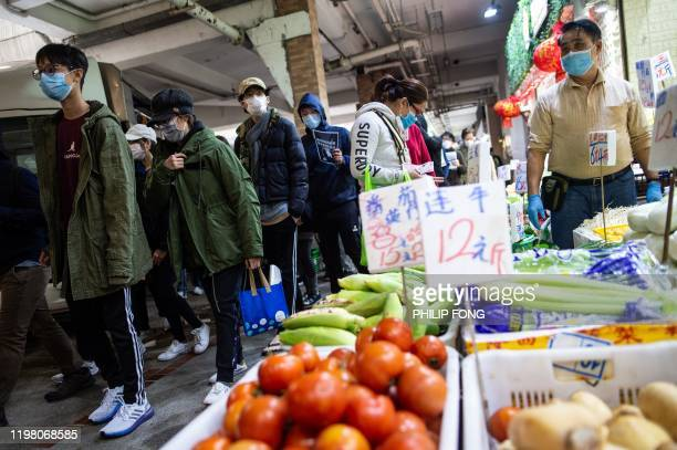 Vegetable stall owner wearing a face mask in a wet market as residents in Mei Foo district protest against government plans to convert the Jao...