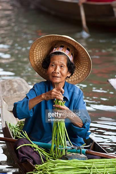 gemüse anbieter in schwimmender markt von damnoen saduak, thailand. - asiatisches langboot stock-fotos und bilder