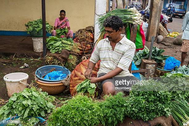 A vegetable vendor cleans vegetables while waiting for customers at a local street market in Mapusa Goa India on Wednesday March 9 2016 While India...