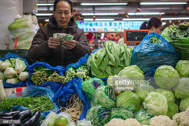 A vegetable vendor is counting money on his stall After rapid growth and development China is facing great challenge of the rising income inequality