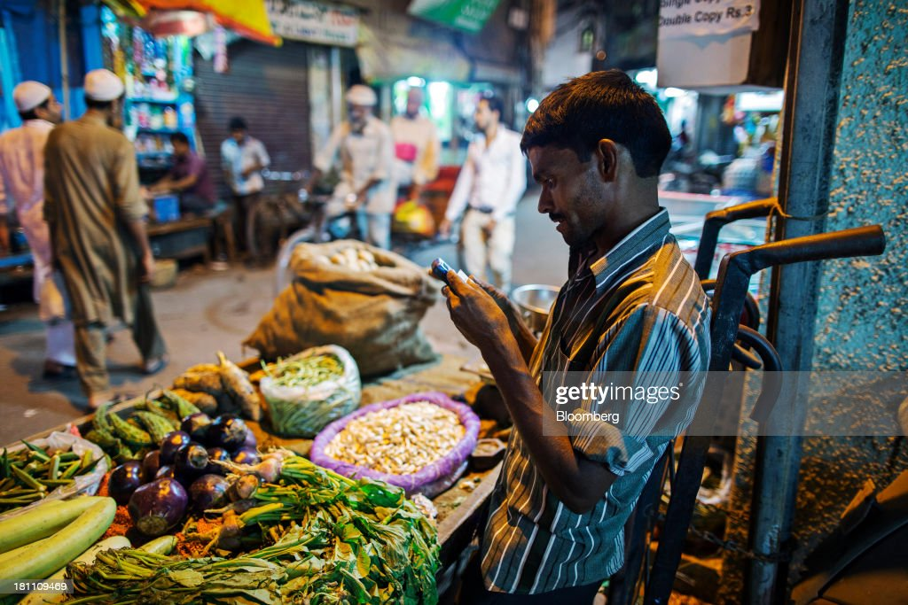 A vegetable vendor uses his mobile phone at his stall in the old Delhi area of New Delhi, India, on Wednesday, Sept. 18, 2013. The Federal Reserves decision to postpone its rollback of U.S. stimulus offered Asian policy makers extra time to address domestic economic fragilities as the region copes with diminished capital inflows. Photographer: Prashanth Vishwanathan/Bloomberg via Getty Images