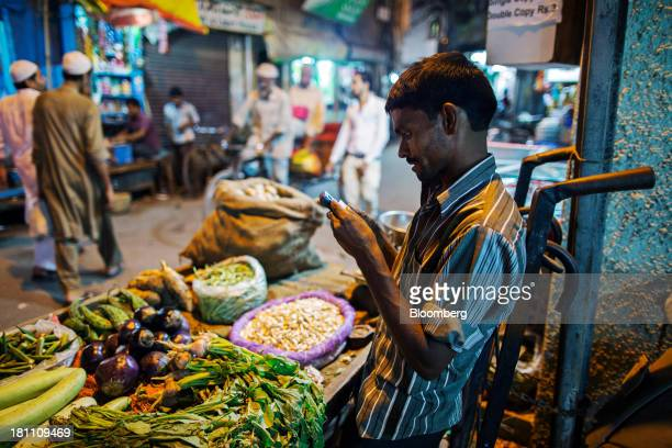 A vegetable vendor uses his mobile phone at his stall in the old Delhi area of New Delhi India on Wednesday Sept 18 2013 The Federal Reserves...