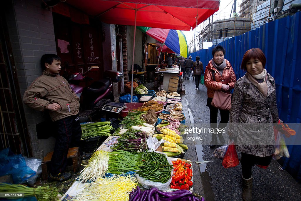 A vegetable vendor waits for customers at an outdoor market on February 5, 2013 in Shanghai, China. Chinese citizens are stocking up on food ahead of the upcoming Chinese Lunar New Year, also known as Spring Festival, is one of the most important festivals in China and falls this year on February 10, 2013.
