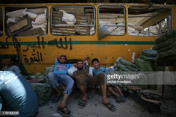 CONTENT] Vegetable vendors rest agains a busturned barricade with visible entrances of sniper bullets August 2013 Aleppo Syria Karaj alHajez crossing...