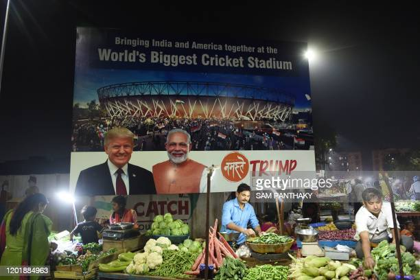 Vegetable vendors wait for customers below a billboard with the images US President Donald Trump and Indian Prime Minister Narendra Modi and the...