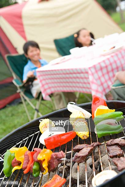 Vegetables and kebabs on barbecue grill, children sitting in background