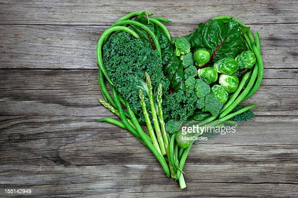 Vegetables - Green Heart Shape on Wood background