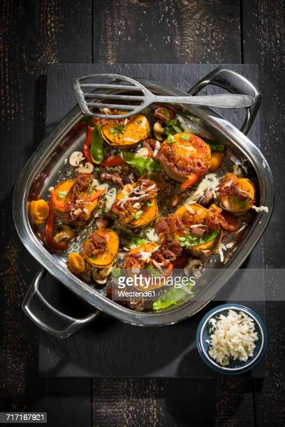 Vegetables, herbs and fried bacon gratinated with cheese in a pan