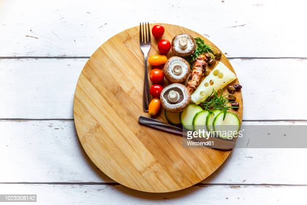 vegetables on round chopping board, symbol for intermittent fasting - dieting stock pictures, royalty-free photos & images