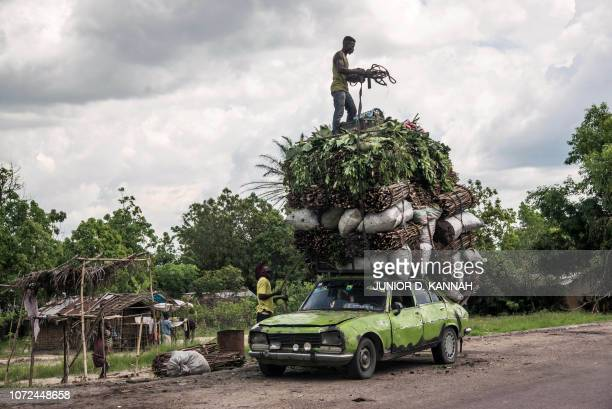 Vegetables, wood and charcoal are loaded onto the roof of a battered Peugeot on November 7, 2018 in Matadi, Democratic Republic of the Congo. - From...