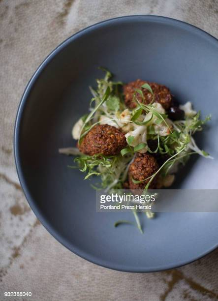 A vegetarian and gluten free dish of roasted chickpea falafel with roast cauliflower with Harissa aioli and plumped flamed raisins at Union...